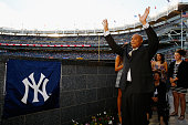 Bernie Williams waves to the crowd prior to unveiling his retired number in Monument Park with his family looking on before the game between the New...