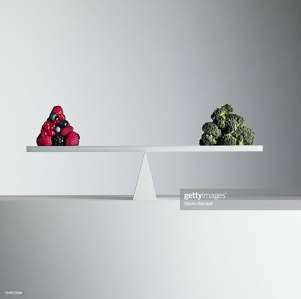 Berries and broccoli balanced on opposite ends of seesaw : Stock Photo