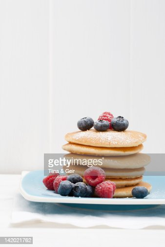 Berries and sugar on stack of pancakes : Stock Photo