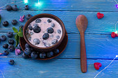 Berries are blueberries and garlands. A celebration for the soul and body. Clay plate and wooden spoon.
