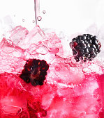 Berry Spritzer Pouring over Ice with Blackberries