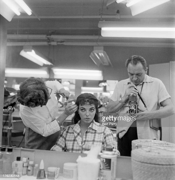 Bert Parry takes a reflection shot as a stylist trims English actress Joan Collins' hair in a film studio 15th August 1955