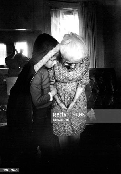 Berto Gonzales whispers a secret to Grandma as he dons his coat to go home She has been friend of children for years providing them with love cookies...