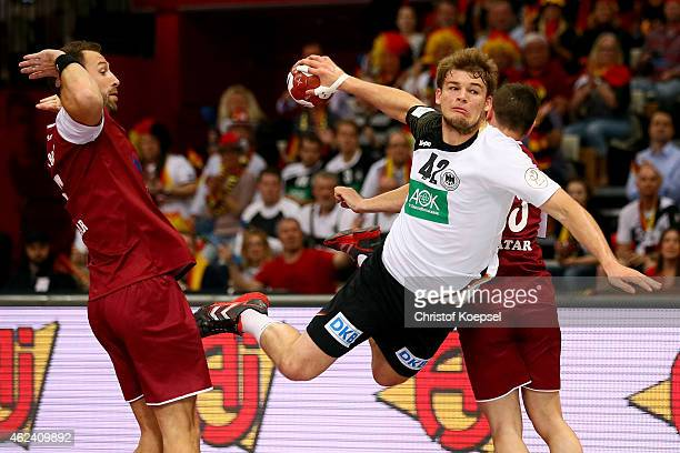 Bertrand Roine of Qatar and Eldar Memisevic of Qatar defend against Paul Drux of Germany during the quarter final match between Qatar and Germany at...