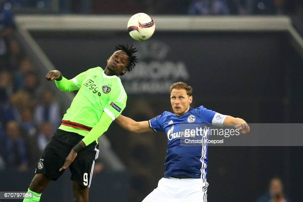 Bertrand Traore of Amsterdam and Benedikt Hoewedes of Schalke go up for a header during the UEFA Europa League quarter final second leg match between...