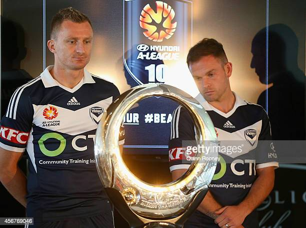 Besart Berisha and Leigh Broxham of the Victory look at the trophy during the ALeague 201415 Season launch at Etihad Stadium on October 7 2014 in...