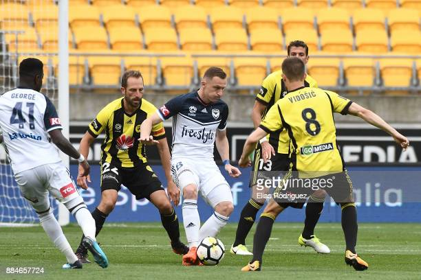 Besart Berisha of Melbourne Victory looks to get past Dario Vidosic and Andrew Durante of the Wellington Phoenix during the round nine ALeague match...