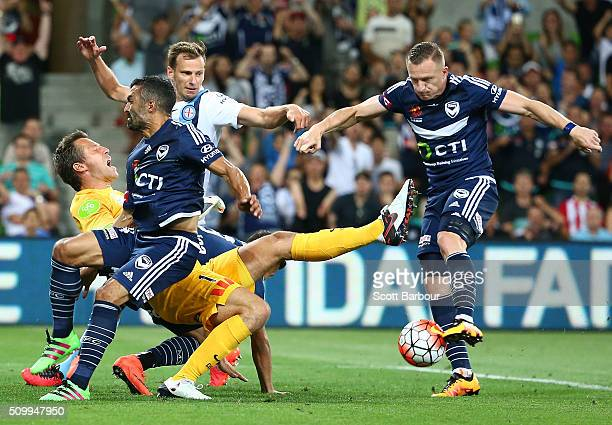 Besart Berisha of the Victory attempts to shoot the ball as goalkeeper Danny Vukovic of City Fc falls to the ground after a Gui Finkler of the...