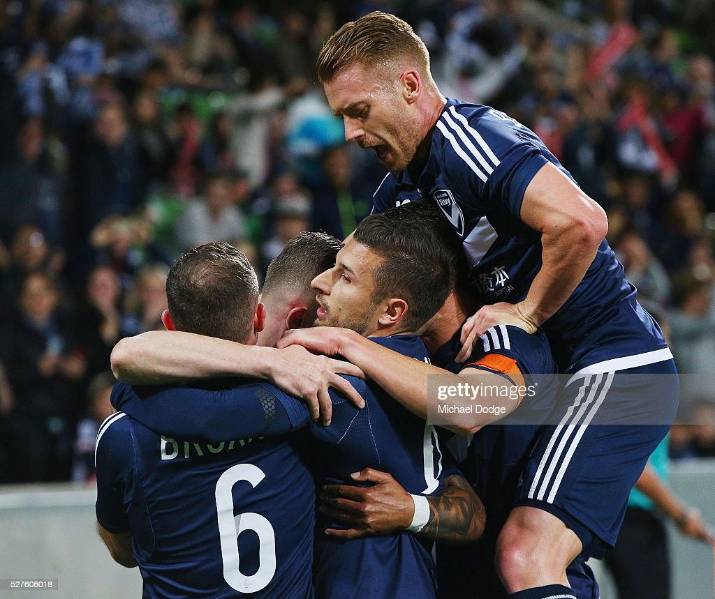 Besart Berisha of the Victory celebrares kicking a penalty goal as teammates jump on during the AFC Champions League match between Melbourne Victory and Gamba Osaka at AAMI Park on May 3, 2016 in Melbourne, Australia.
