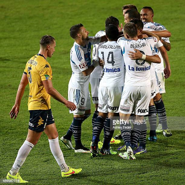 Besart Berisha of the Victory celebrates a goal with team mates with Zachary Anderson of the Mariners looking dejected in frame during the round 10...