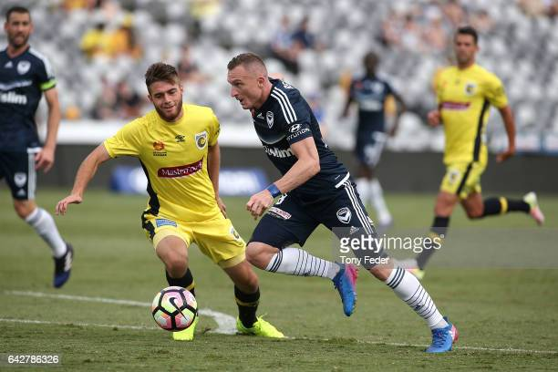 Besart Berisha of the Victory contests the ball with Liam Rose of the Mariners during the round 22 ALeague match between the Central Coast Mariners...