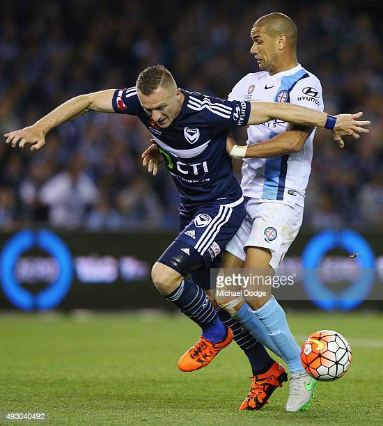 Besart Berisha of the Victory is tripped up by Patrick Kisnorbo of the City during the round two ALeague match between Melbourne Victory and...