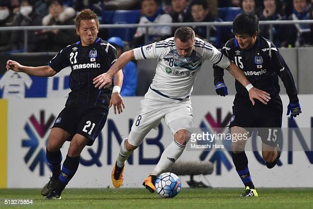 Besert Berisha of Melbourne Victory and Yosuke Ideguchi Yasuyuki Konno of Gamba Osaka compete for the ball during the AFC Champions League Group G...