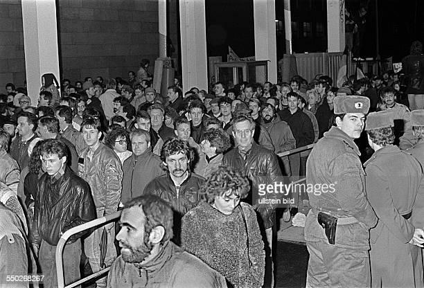 Besetzung der StasiZentrale in der Normannenstrasse Buerger stroemen durch das Tor Volkspolizisten schauen zu
