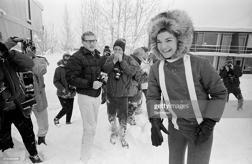 Besieged by photographers, Jacqueline Kennedy calls to her children playing in the snow during a vacation in Aspen.