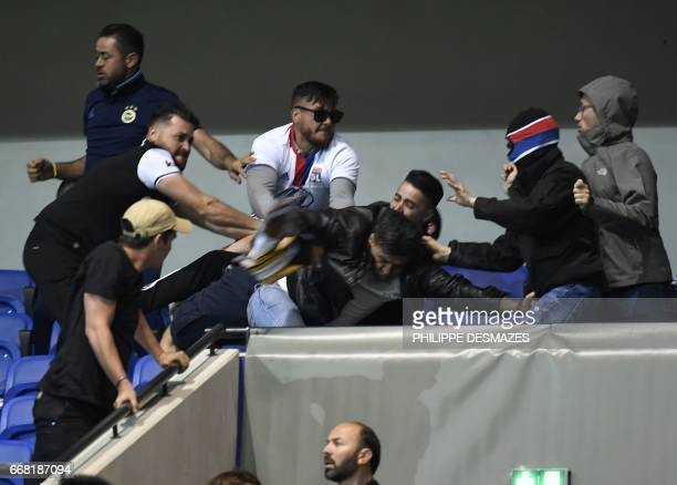 Besiktas' and Lyon's supporters fight before the UEFA Europa League first leg quarter final football match between Lyon and Besiktas on April 13 at...