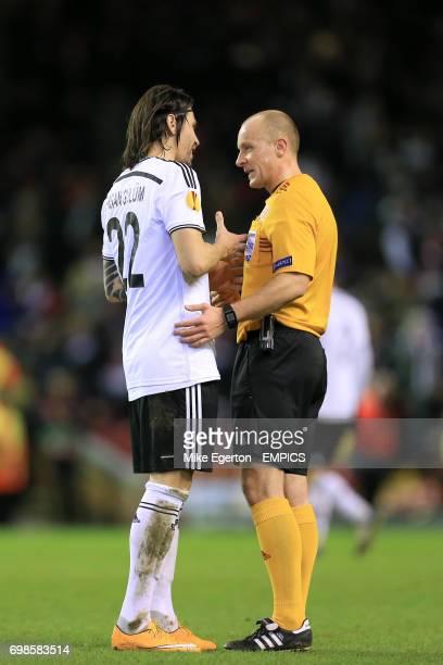 Besiktas' Ersan Gulum argues with referee Szymon Marciniak