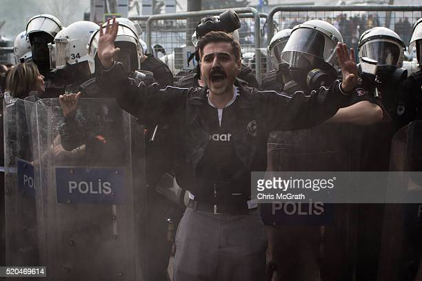 Besiktas fan tries to calm people down after police used tear gas to disperse fans trying to enter the stadium for the opening match of the new...