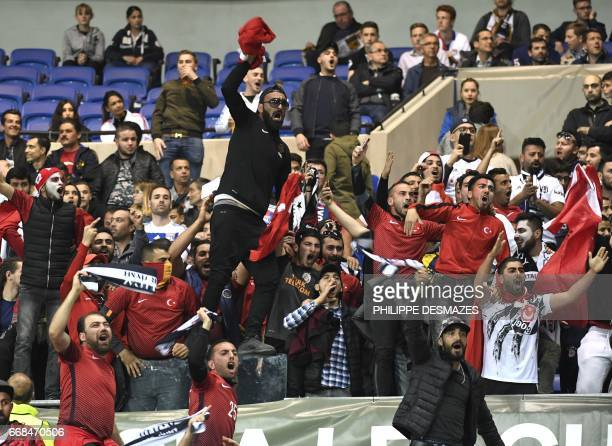 Besiktas' fans gesture and shout against Lyon's fans as they stand in the tribune before the Europa League football match Olympique Lyonnais against...