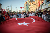 Besiktas football club supporters hold a giant Turkish national flag as they shout slogans during a protest against the military coup on Taksim...