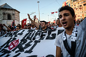 Besiktas football club supporters shout slogans and hold a banner reading 'we are against tanks and weapons' during a protest against the military...