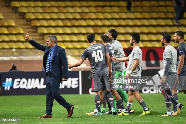 Besiktas' head coach Senol Gunes and Besiktas' players react after winning the UEFA Champions League group stage football match between Monaco and...