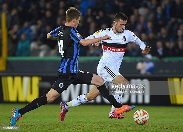 Besiktas' midfielder Oguzhan Ozyakup drives the ball past Club Brugge's defender Brandon Mechele during in the UEFA Europa League round of 16 match...