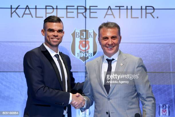 Besiktas' new transfer Pepe and Besiktas' President Fikret Orman shake hands as they pose for a photo during a signing ceremony at Vodafone Park in...