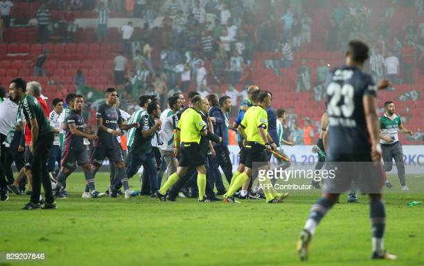 Besiktas' Portuguese defender Pepe and Brazilian defender Adriano leave the pitch with referees as football fans invade the pitch during the Turkish...