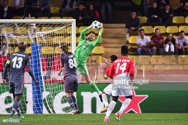 Besiktas' Spanish goalkeeper Fabricio Agosto Ramirez grabs the ball under pressure from Monaco's Colombian forward Radamel Falcao and Monaco's...