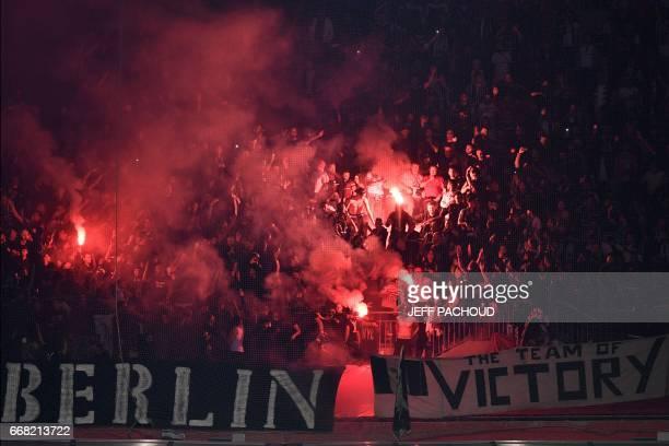 TOPSHOT Besiktas supporters burn flares during the UEFA Europa League first leg quarter final football match between Lyon and Besiktas on April 13 at...