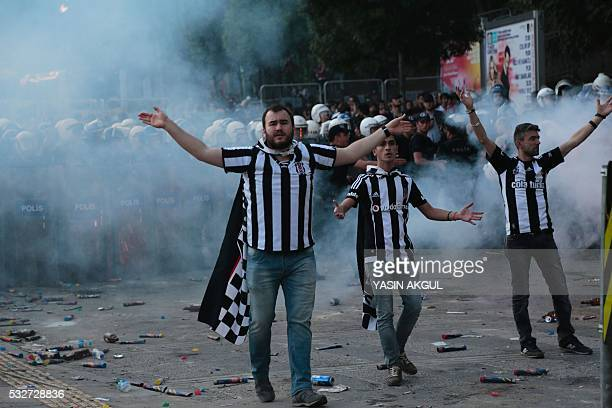 Besiktas' supporters react as Turkish police use tear during celebrations after their team won the Turkish Super Toto league football match between...