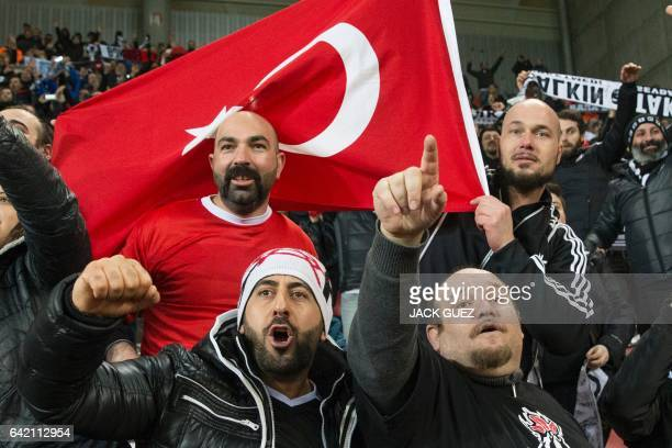 Besiktas's supporters one with a Turkish national flag cheer up their team during the UEFA Europa League football match Hapoel Beer Sheva vs Besiktas...