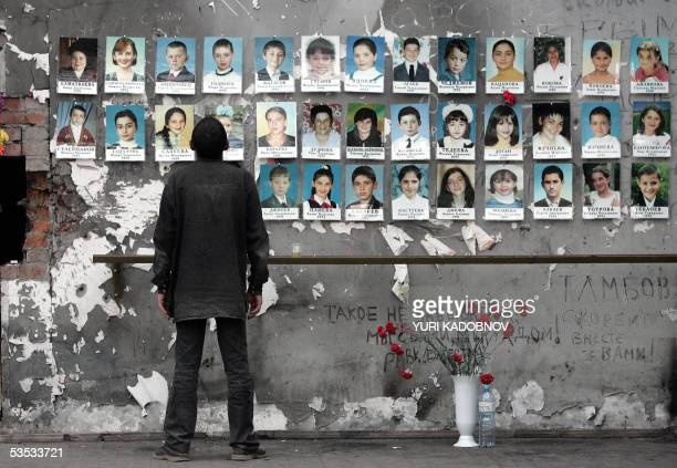 A man looks at pictures of children killed last year in the school sports hall of Beslan 30 August 2005 Russia marks 01 September the oneyear...