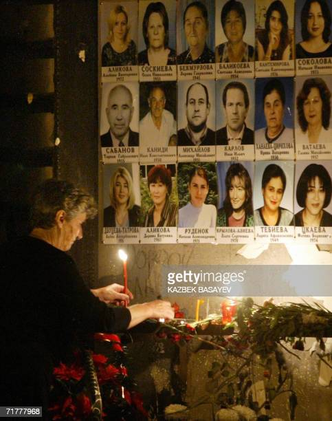 A woman lights a candle at a wall of the destroyed school gymnasium decorated with pictures of the victims during a ceremony in memory of the Beslan...