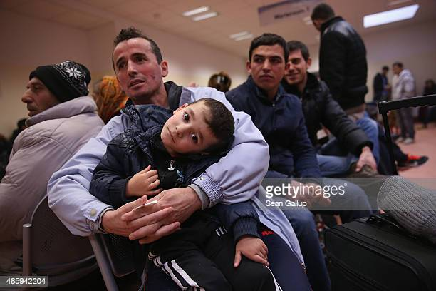Besnek a migrant from Albania holds his son Enek as he and others wait to register at the Central Registration Office for Asylum Seekers of the State...