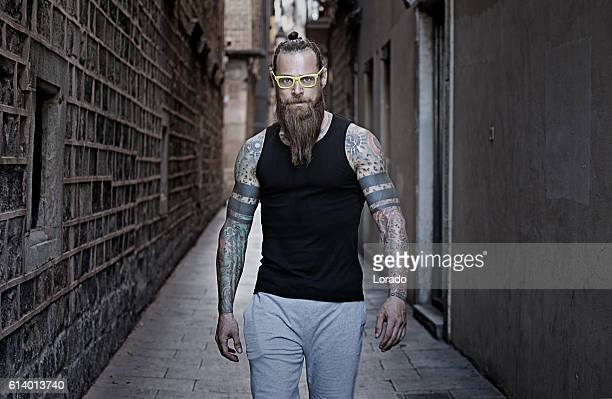 Bespectacled bearded handsome male posing in an urban setting
