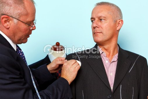 Bespoke suit adjustment by a tailor : Stock Photo