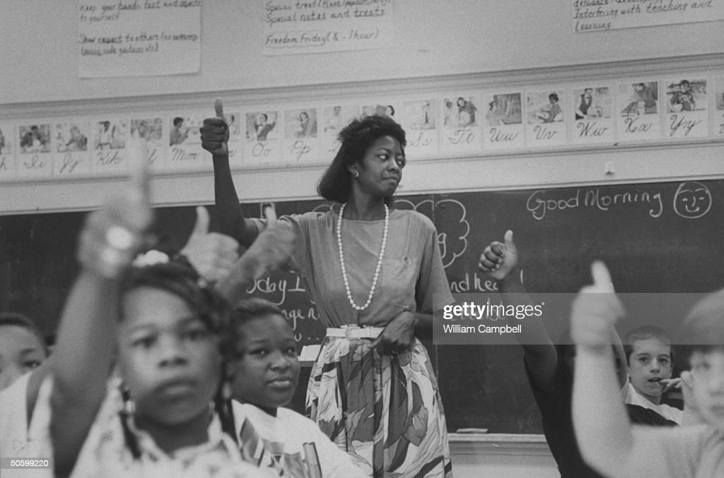 Bessie Pender, a former school janitor who put herself through college to become a teacher, flashing thumbs-up sign as her students do the same in classroom at Coleman Place Elementary school where Pender now teaches.