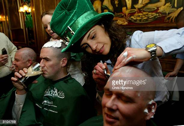 Bessy Sidiropoulos of Greenwich Connecticut shaves the head of Gary Ludden during a St Baldrick's Day event at Jim Brady's Pub March 17 2004 in New...