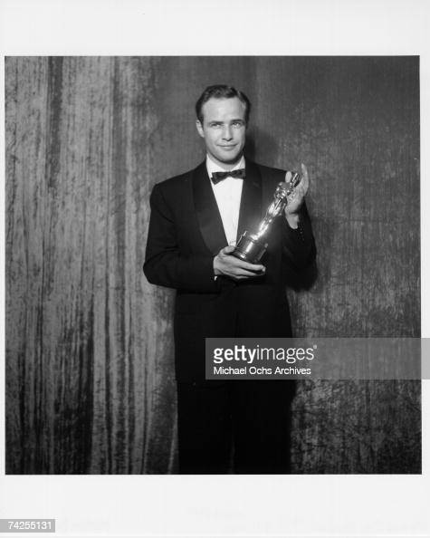 Best actor winner Marlon Brando poses backstage at the 27th Academy Awards holding an Oscar for his performance in the movie 'On The Waterfront' on...