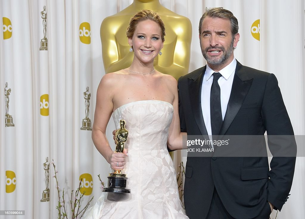 Best Actress winner Jennifer Lawrence celebrates in the press room for her role in 'Silver Linings Playbook' with Jean Dujardin (R), who won Best actor in 2012, during the 85 Academy Awards on February 24, 2013 in Hollywood, California. AFP PHOTO / Joe KLAMAR