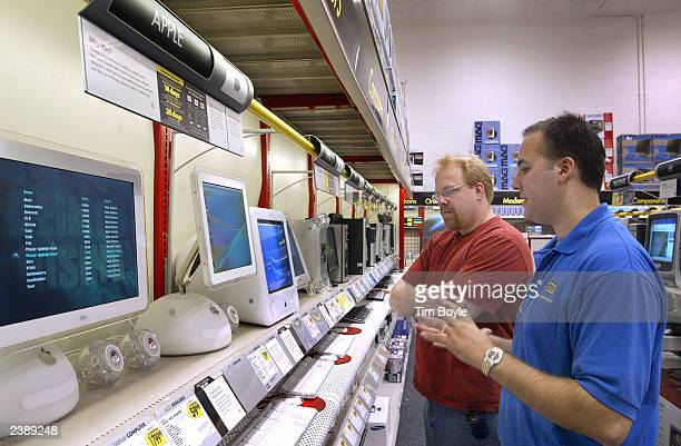 Best Buy employee Jonah Aldrete talks with shopper Phil Gersdorf about the new Apple desktop computers displayed at a Best Buy store August 11 2003...