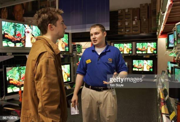 Best Buy employee Walter Slavnov assists Nick Hehn as he shops for flatpanel wide screen televisions at a Best Buy store January 31 2006 in Niles...