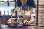 Part of young cheerful African woman in apron holding coffee cups while standing at cafe