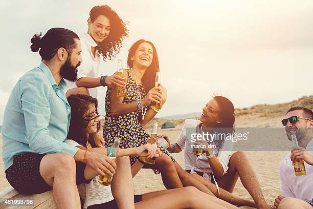 Best friends drinking beer at the beach