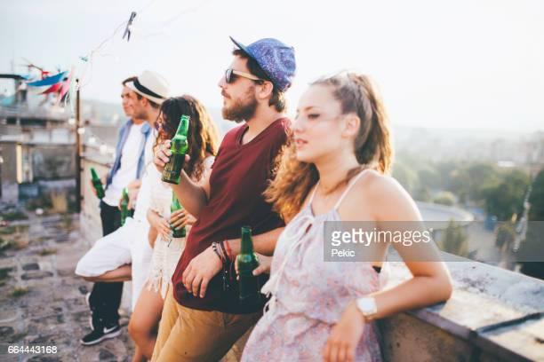 Best friends drinking on a rooftop party