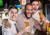Best friends in a bar. Men shout and rejoice in meeting and drink beer. Three other men drinking beer and having fun together in the bar