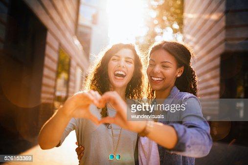 Migliori amici di ridere mentre mostrando il cuore con le mani