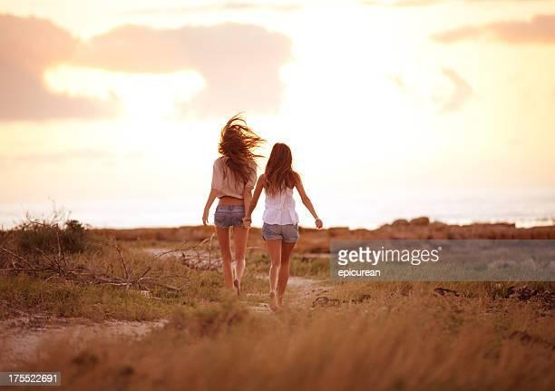 Melhores amigos correr juntos no pôr do sol de mãos dadas
